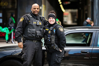 photo of two sheriff officers standing in front of a car